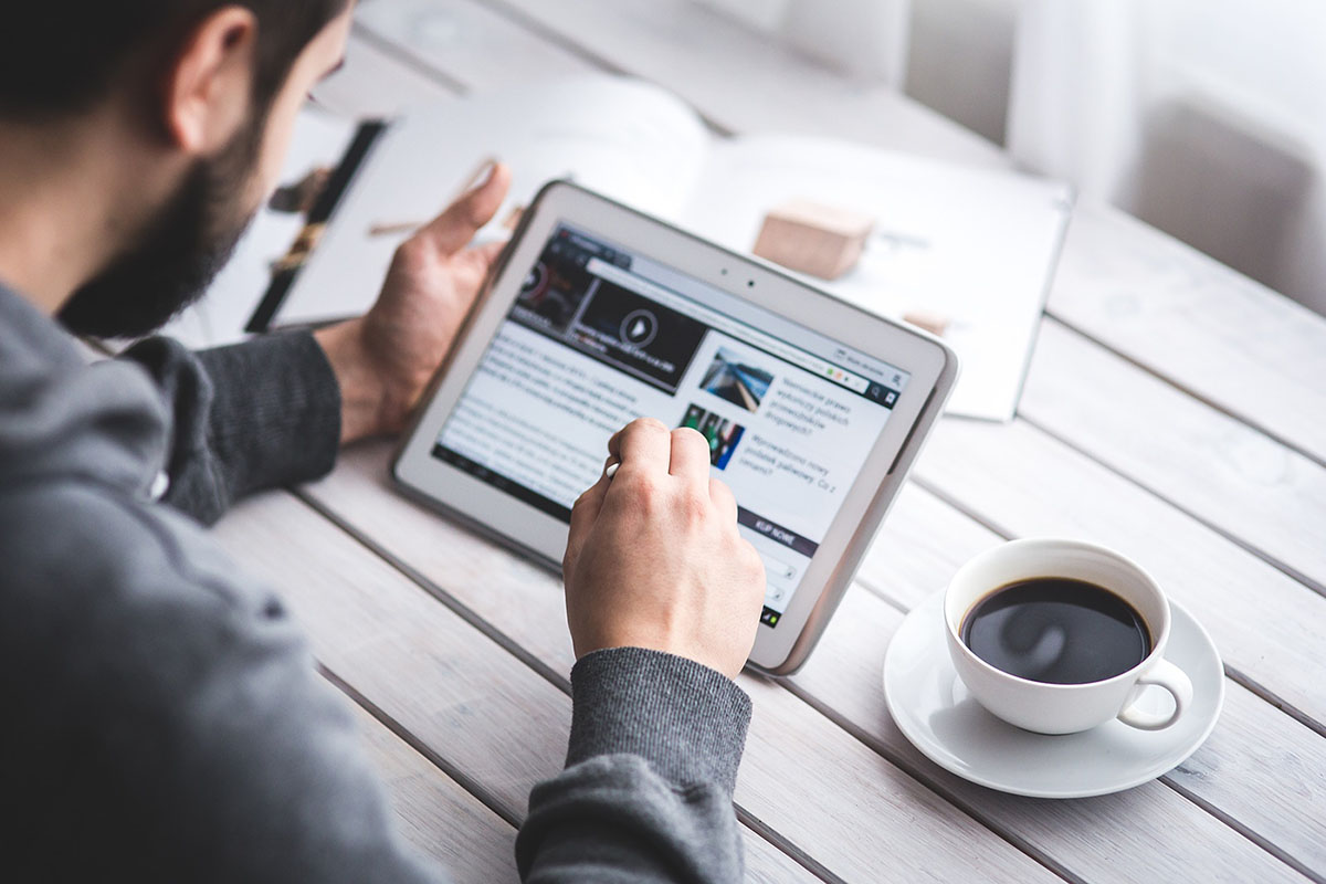 man looking at website on tablet with coffee and books nearby