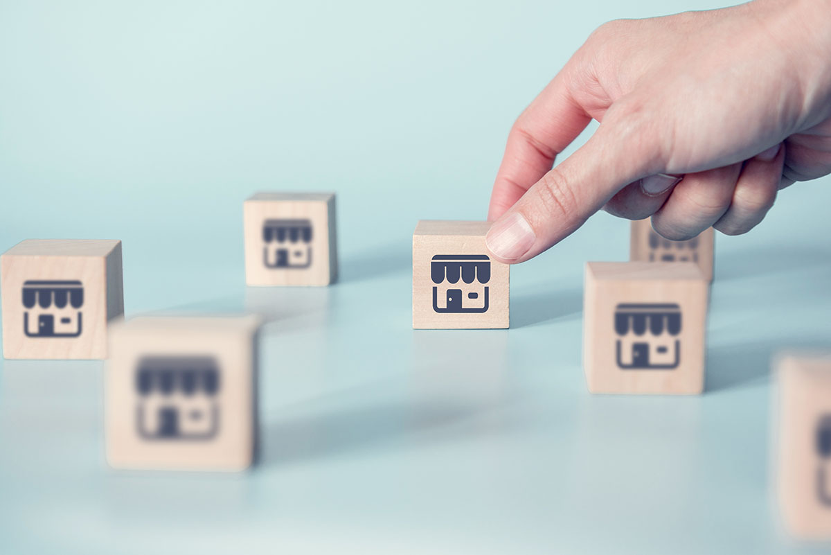 hand setting down cube with GMB icon printed on outside surrounded by other cubes